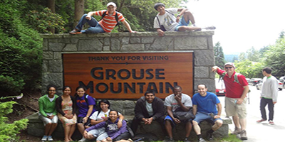 a group of people siting around a Grouse Mountain sign